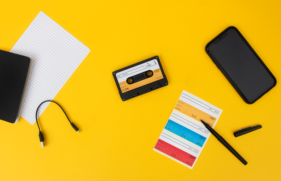 Cassette tape speaker on yellow desk with phone, stickers and charging cable