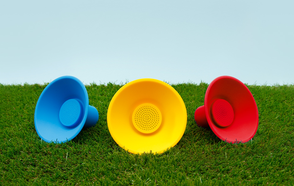 Blue, yellow and red icon speakers on grass