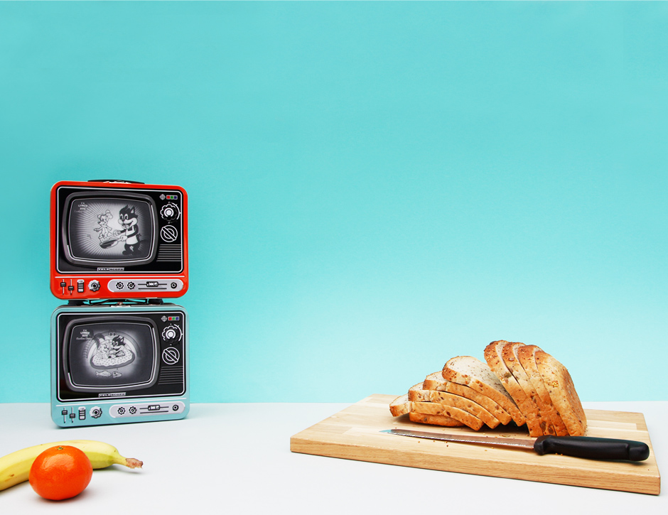 Orange and blue tv lunchboxes with fruit and bread board