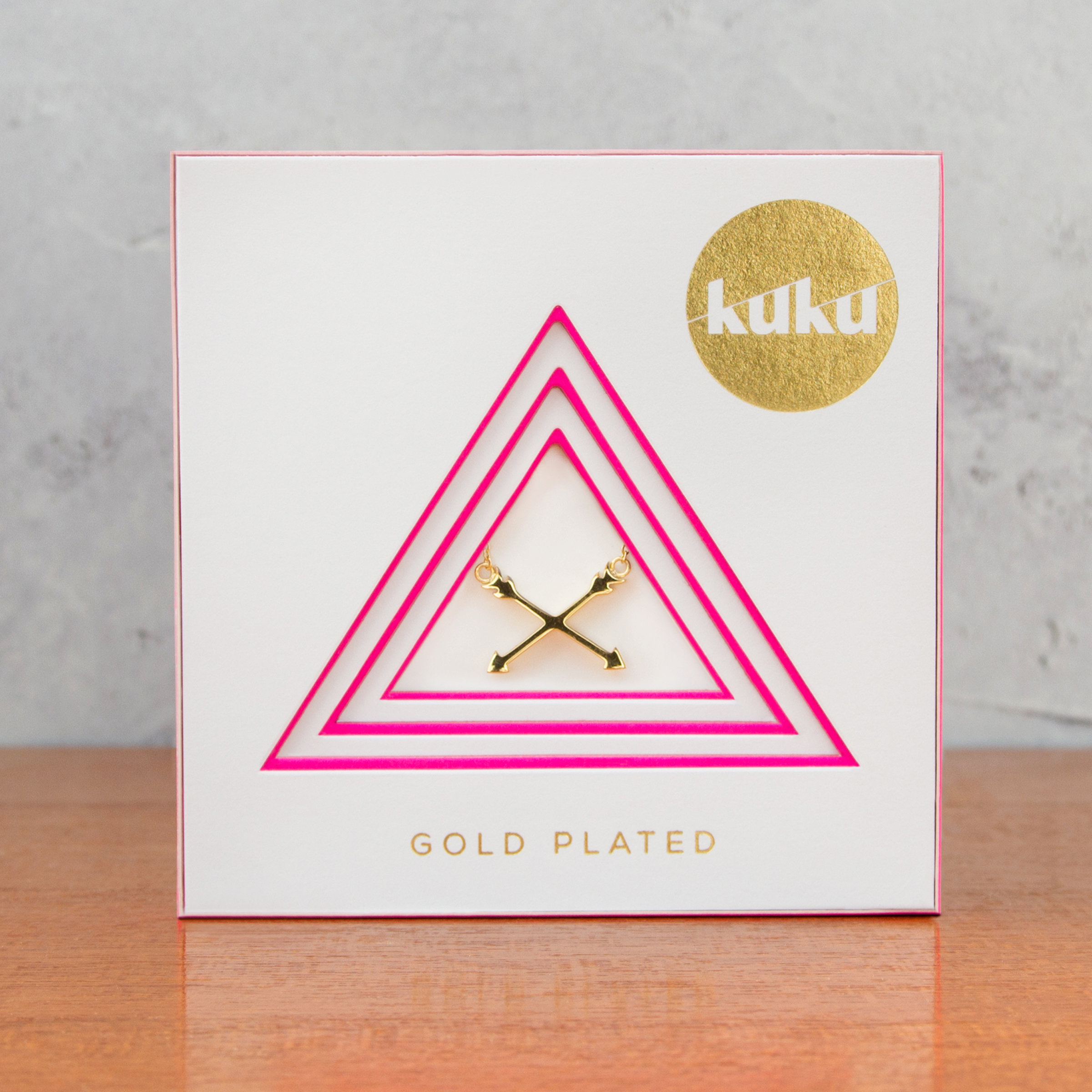 Kuku gold arrow necklace in packaging
