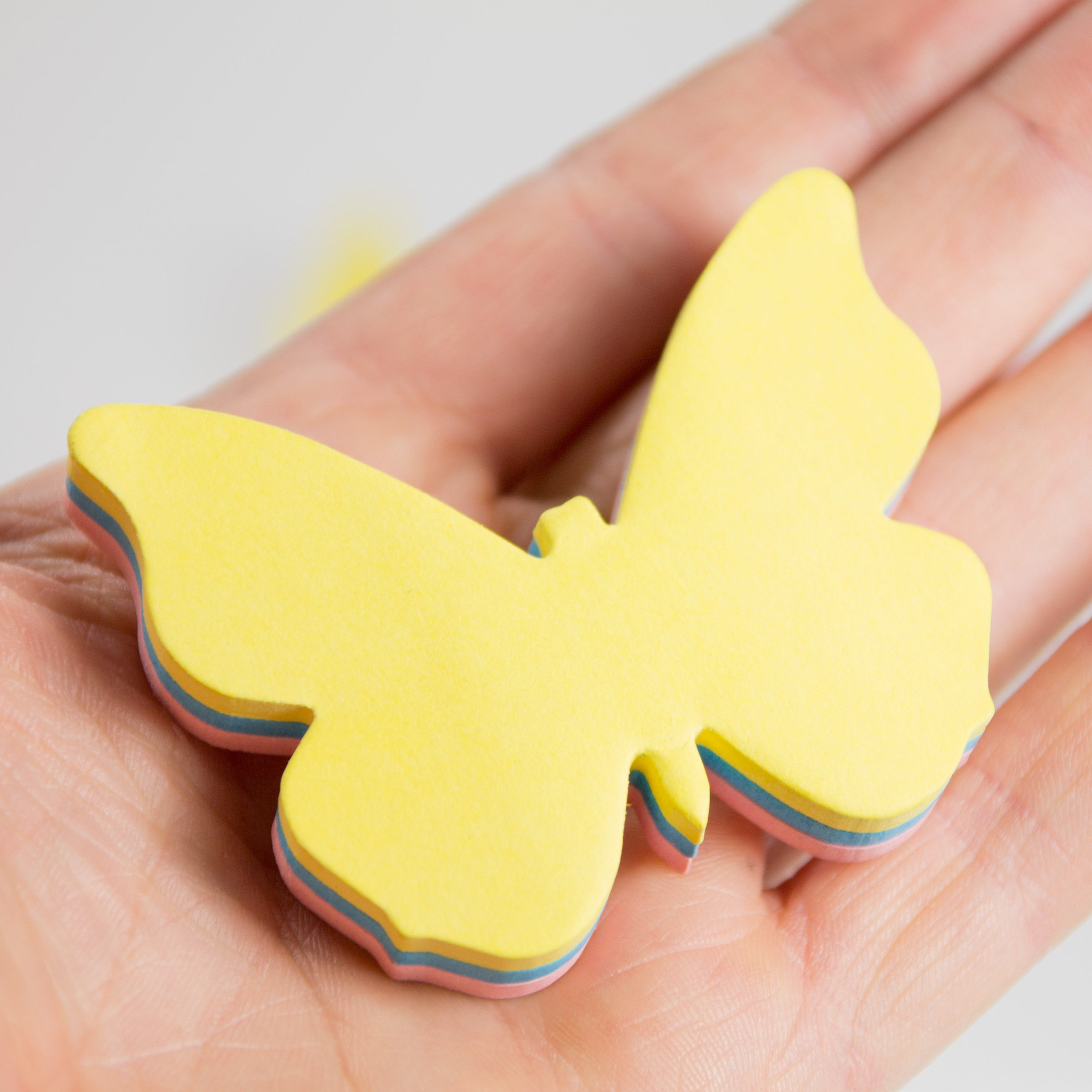 Butterfly sticky note pads in a hand