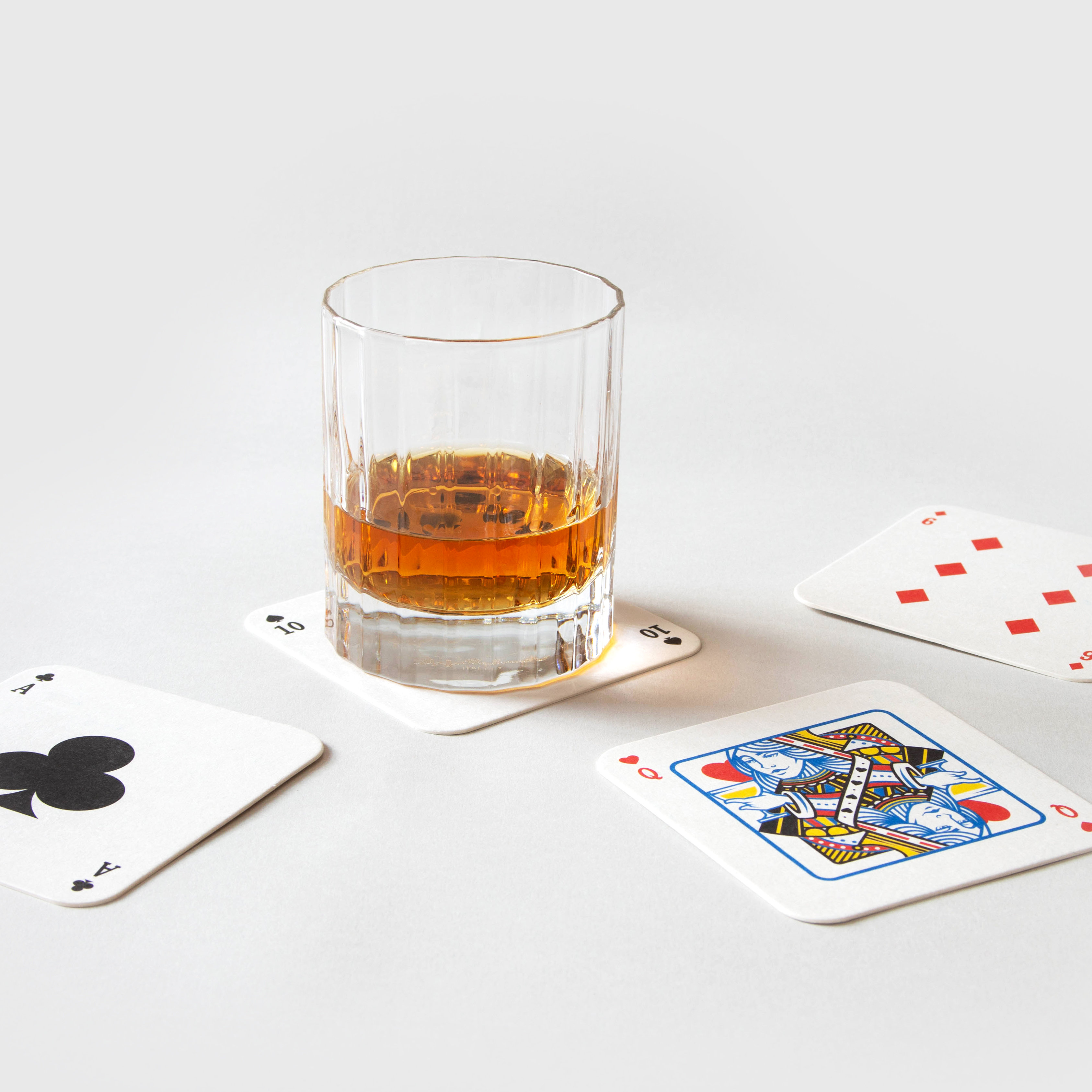 Glass of whiskey on playing mat coasters