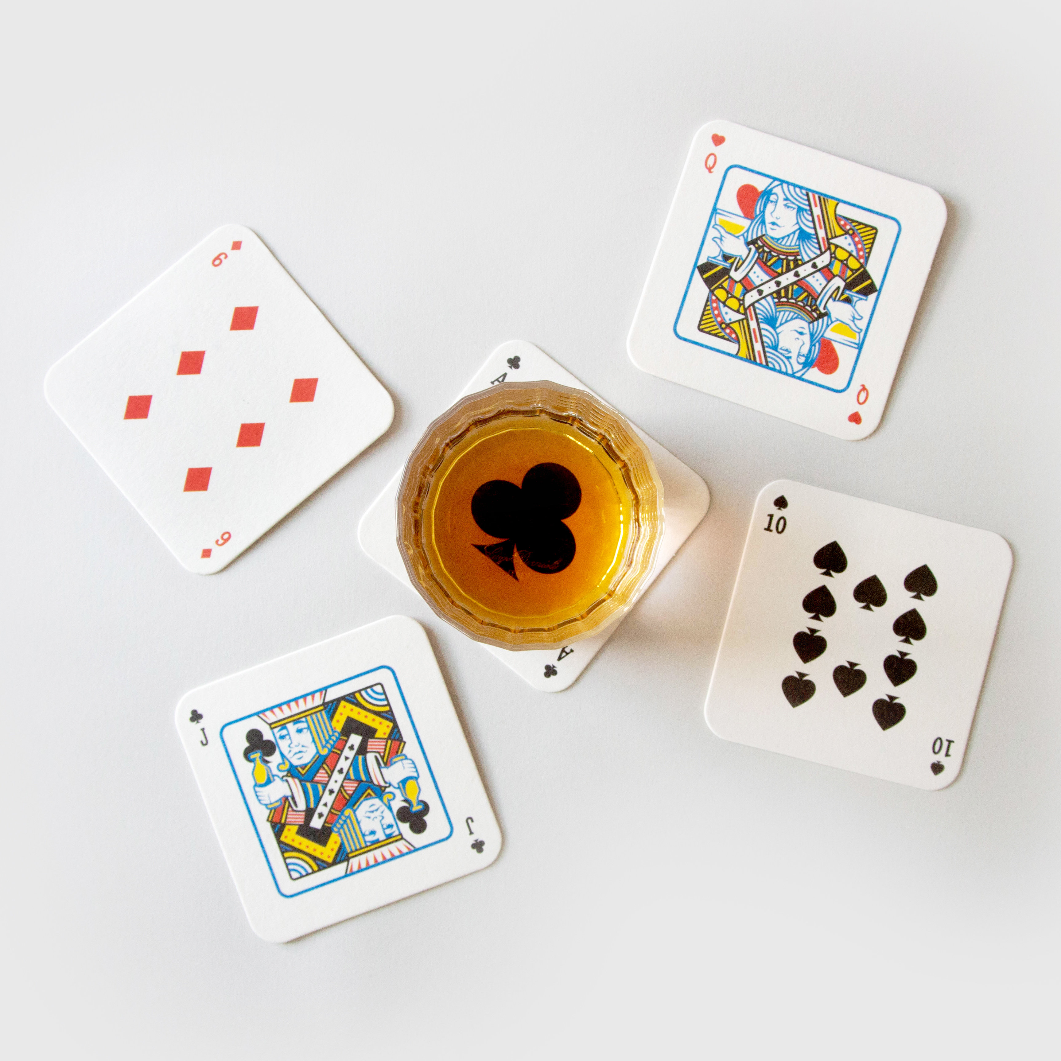 Glass of whiskey on drink mat playing cards