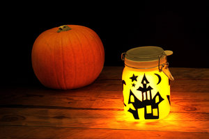 Halloween sun jar on a table next to pumpkin