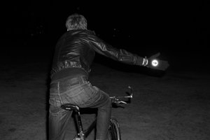 Man riding a bike and indicating wearing reflective cycling gloves