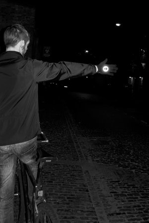 Man indicating at night wearing highly reflective bike gloves