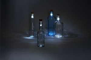 White LED Bottle Lights in empty glass bottles in the dark.