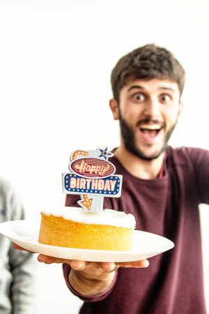 Man holding birthday cake with neon sign on top