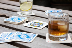 Playing cards at the pub with drink mats