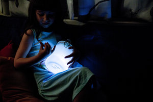 kid holding light jar at night