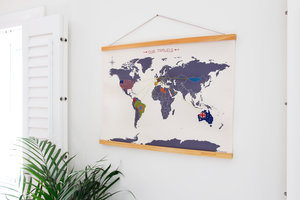 cross stitch map on a white wall with window shutters