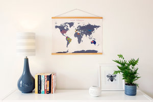 cross stitch map on a living room wall with books and a lamp