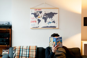 cross stitch map of the world above man reading book