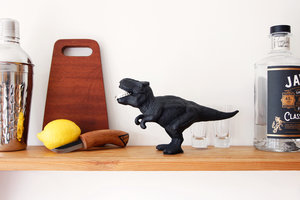 t-rex dinosaur bottle opener on shelf with gin and lemon