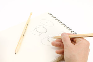 Drawing drums with wooden pencil.