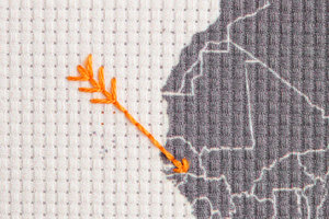 embroidered world map arrows close up