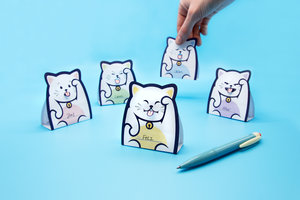 Folded lucky cat memo notes with hand