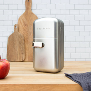 Fridge shaped food container closed on wooden worktop with tiles