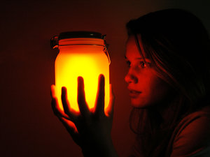girl holding mason jar in the dark