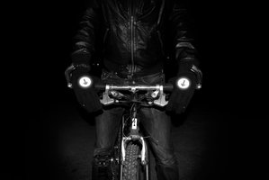 Man holding bicycle handle bars wearing reflective biker gloves
