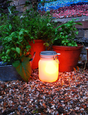 glow jars in the garden near flower pots