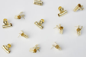gold push pin clips on a grey background