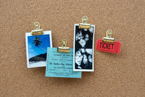 gold push pins on a cork pin board with tickets and photos