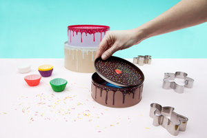 Hand removing lid from small cake storage tin
