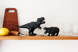dinosaur and hippo cast iron bottle opener on shelf