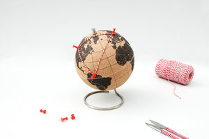large cork globe with pins and thread
