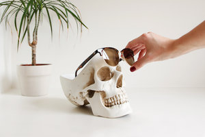 woman removing sunglasses from skull desk organizer