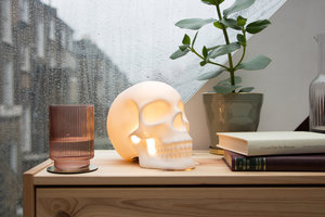 Skull table lamp on bedside table with rain on the window