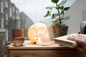 Skull lamp with hand taking book