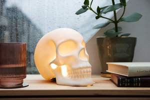 Close up view of Skull table lamp on bedside table with rain on the window