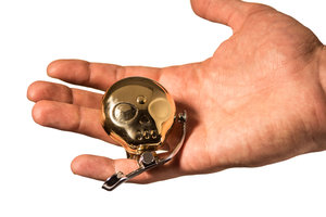 A tough skull shaped compact brass bell with sprung thumb lever