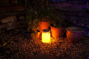 solar light jar in garden darker